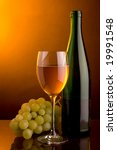 a glass of white wine and grape and green bottle - stock photo