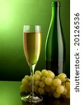 a glass and a bottle of white wine and green grape - stock photo