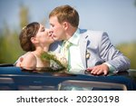 Bride and groom kissing on wedding auto - stock photo