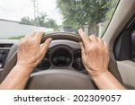 Senior woman driving a car slowly in town - stock photo