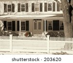 This is a sepia toned shot of a comfy home with a white picket fence. - stock photo