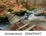 old broken bridge of planks over the river with stones and moss in the forest near the mountain slope - stock photo