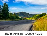asphalt road going to high mountains down the hill and  passes through the green shaded forest at sunrise - stock photo