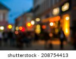 A crowd of people moving on the old european city night street defocused blurred abstract image - stock photo