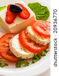tomato and cheese slices with olive and salad on plate - stock photo
