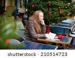 Girl writing Christmas postcards in an outdoor Parisian cafe - stock photo