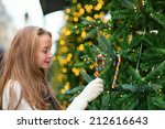 Beautiful girl decorating Christmas tree with colorful candies - stock photo