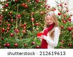 Girl with a Christmas present near the Christmas tree - stock photo