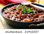 A pan of chilli, ready to serve.  Soft focus, shallow depth of field. - stock photo