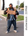 a homeless person with a cardboard sign, showing first hand the plight of the homeless in california - stock photo