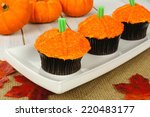 Pumpkin cupcakes on a plate with burlap on a wooden table            - stock photo
