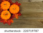 Cluster of autumn leaves and pumpkins against aged wood background     - stock photo