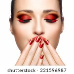 Trendy Red Makeup. Beautiful young woman with hands on her face covering mouth. Perfect skin. Festive Nail art and makeup concept. High Fashion Portrait. - stock photo