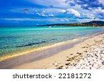 Kitesurfers gliding at high speed around the beach Cinta, Sardinia - stock photo