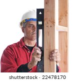 Carpenter with level checking vertical plumb of studs isolated over white - stock photo