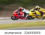 Two Motorcycles practice leaning into a fast corner on track - stock photo