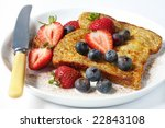 French toast with strawberries, blueberries, and cinnamon.  A delicious, healthy breakfast. - stock photo