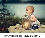 Portrait of a small baby girl at a Lake in the evening with glowing lantern - stock photo