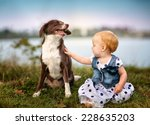 Portrait of a small baby girl at a Lake with a Dog - stock photo