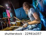 Drummer playing on drum set on stage. Warning - authentic shooting with high iso in challenging lighting conditions. A little bit grain and blurred motion effects. - stock photo