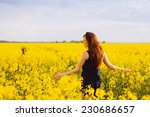 Young woman in sleeveless dress enjoying sunlight and nature on yellow blooming rapeseed field - stock photo