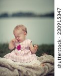 Portrait of a unhappy small baby girl at a Lake - stock photo