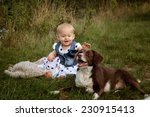 Portrait of a small baby girl at a Lake with her friendly dog pet - stock photo