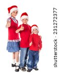 Three happy kids in Christmas hats with thumbs up sign - stock photo