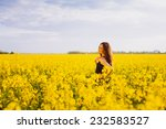 Side view of young woman with long hair touching her shoulder on yellow blooming rapeseed field - stock photo