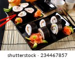 sushi set with salmon,avocado and cucumber on black plates - stock photo