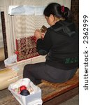 Handmade weaving of a silk rug on an ancient loom in a Factory, China - stock photo