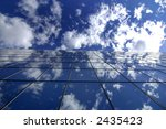 Wall of office building with mirror windows reflecting blue sky and clouds - stock photo