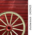 Detail of old wagon wheel and red wall in background - stock photo