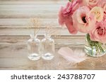 Still life with pink Eustoma flowers in a vase with fearher and two glass botles - vintage look - stock photo