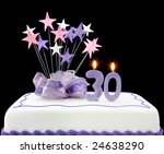 Fancy cake with number 30 candles.  Decorated with ribbons and star-shapes, in pastel tones on black background. - stock photo