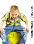 The boy the blonde sits on a stool. - stock photo