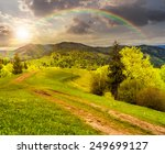 composite mountain landscape with  road on hillside meadow few fir trees and forest  on both sides of the road in sunset light with rainbow - stock photo