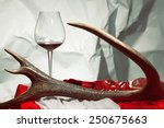 Aristocratic supper concept. Glass of red wine with fresh bushmeat on white plate and pomegranate served with baroque accessories: deer antler, red & white sheets. Vintage style. Close up. Indoor shot - stock photo