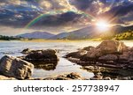 composite landscape with rocky lake shore and some boulders in mountains in sunset light with rainbow - stock photo