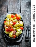 Potato with fresh tomato and garlic on barbecue dish - stock photo
