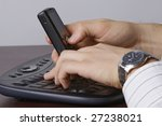 A man working on a laptop, holding a cellular phone in one hand - stock photo