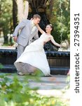 Groom and bride joy against backdrop fountain - stock photo