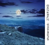 view on high mountains from hillside covered with grass with few stones on the edge at night in full moon light - stock photo