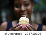 Close up of African American women's hands holding cupcake â?? selective focus on cupcake with blurred face on background - stock photo