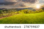 summer rural landscape. fence near the meadow and trees on the hillside. forest in fog on the mountain top in sunset light - stock photo