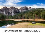 composite landscape with CGI elements. lake with boulder on the shore near the pine forest in mountains with 3D stone peaks - stock photo