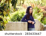Young woman with long dark hair leaning on stone wall posing during stroll in park - stock photo