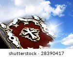 bible with white cross over blue sky with light flare - stock photo