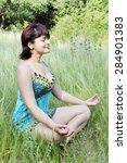 woman meditating on the grass in a forest glade - stock photo