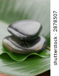 two stones on top of each other on green leaf - stock photo